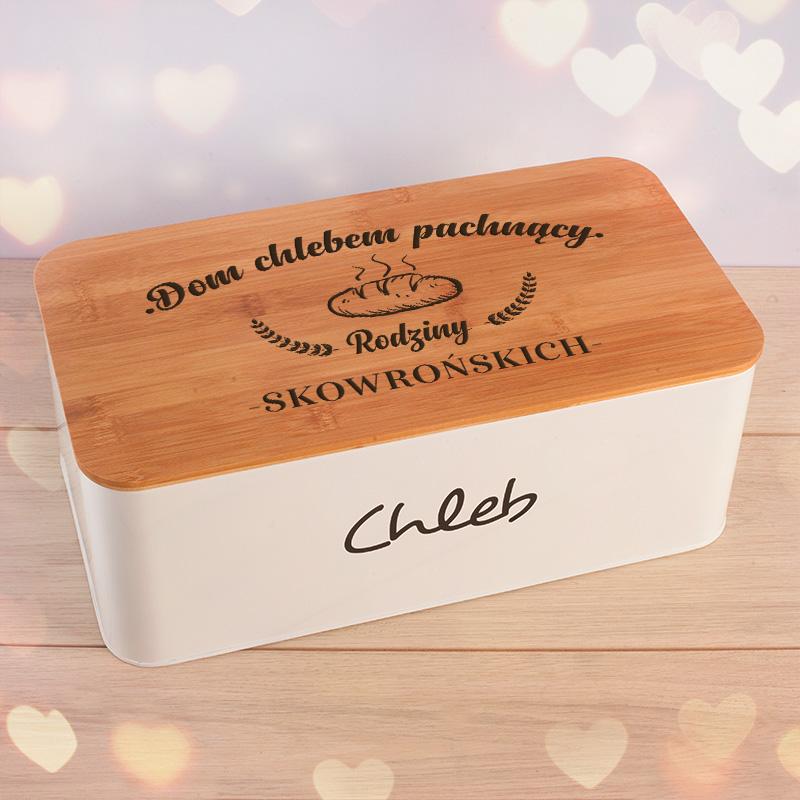 Metalowy, kwadratowy chlebak z drewnianą pokrywą, na której znajduje się grawer z dekoracyjnym napisem oraz nazwiskiem. Chlebak ma biały kolor i napis na ściance chleb. Drewniana pokrywa może posłużyć również jako deska kuchenna.