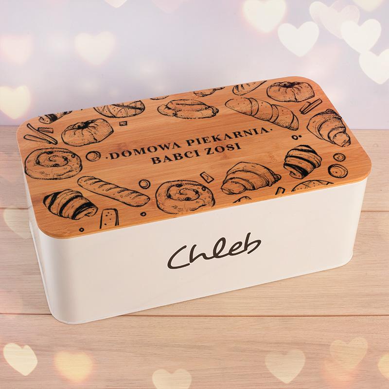 Metalowy, duży chlebak z drewnianą pokrywą, która zawiera personalizowane zdobienie. Przykrywka jets także deską do krojenia. Pudełko ma biały kolor, jest metalowe, z napisem chleb.