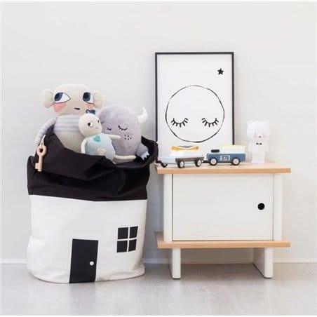 Worek na zabawki dziecka w kształcie domku w biało-czarnej kolorystyce. Ma na górze ściągacz, dzięki czemu się zamyka.