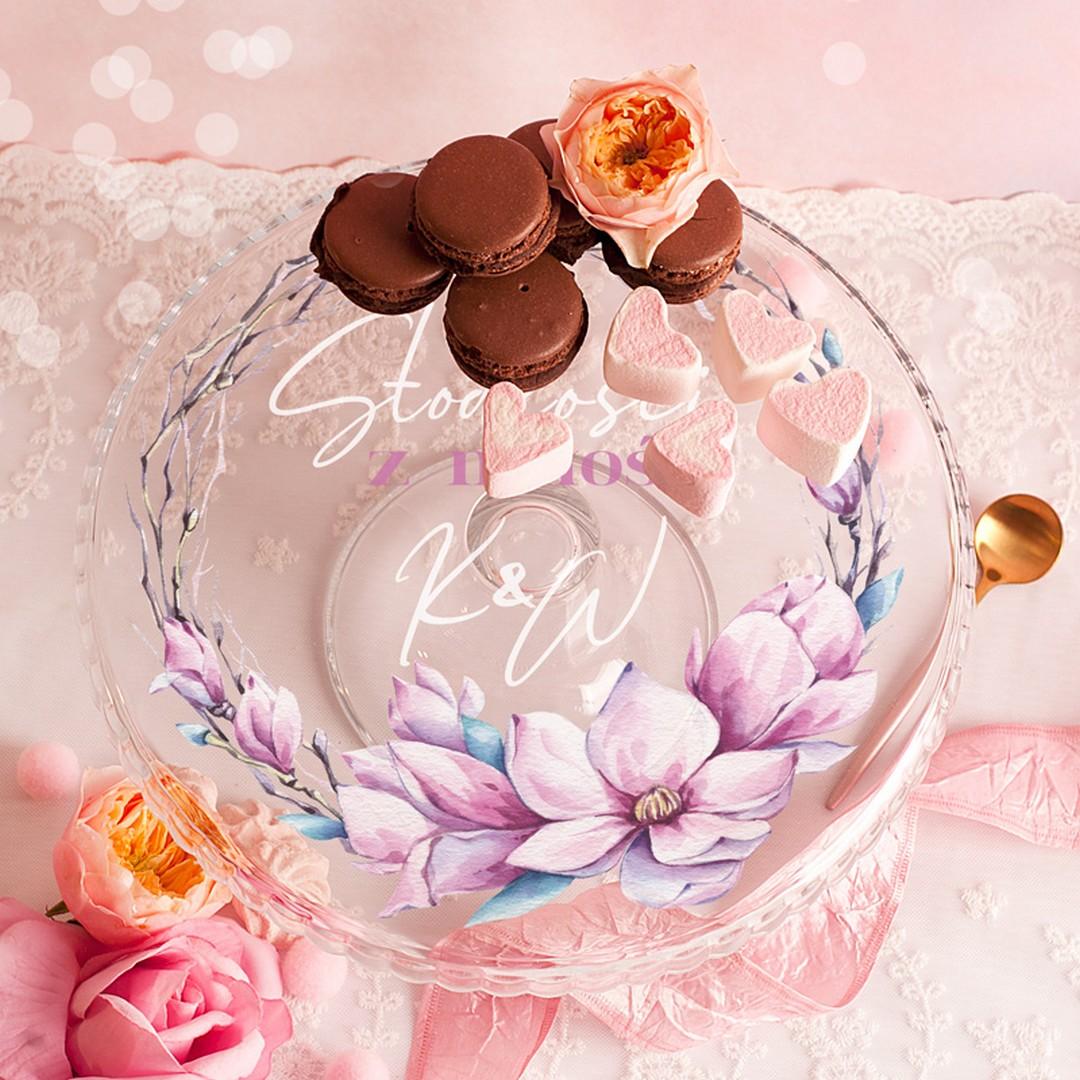patera ze zdobieniem w postaci wianuszka uwieńczonego pięknymi kwiatami magnolii. Wewnątrz dekoracji kwiatowej na płaszczyźnie patery znajduje się miła dedykacja Słodkości z miłości zakończona podpisem czyli inicjałami pary młodej dla której jest ten prezent