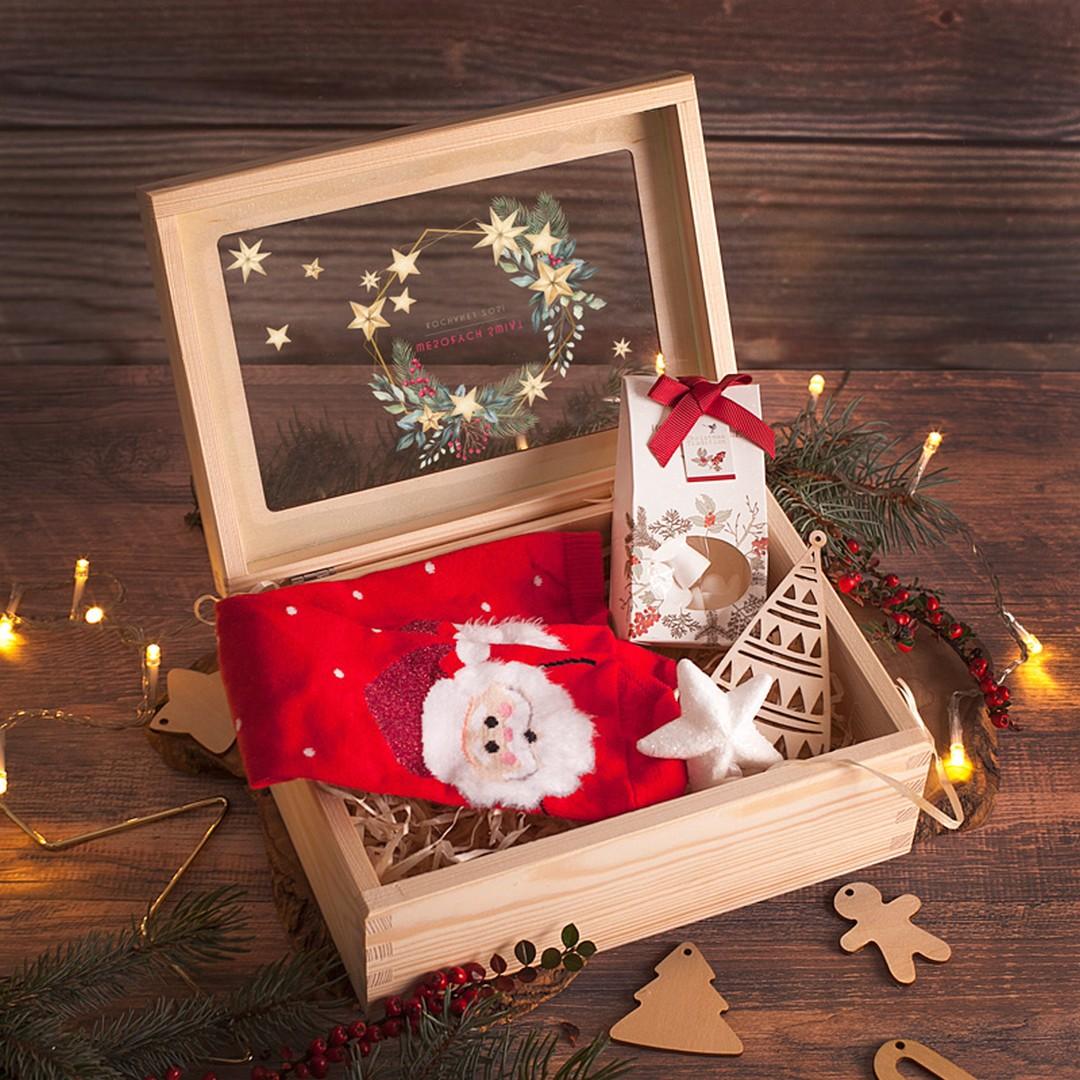 Drewniana skrzynka z szybką, wewnątrz której znajduje się zestaw świątecznych upominków