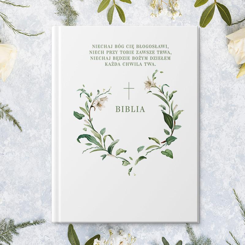 Pamiątka chrztu jaką jest Biblia z personaliizowaną okładką, na której widnieje imię dziecka oraz dedykacja w otoczeniu pięknej dekoracji z kwiatów lilii