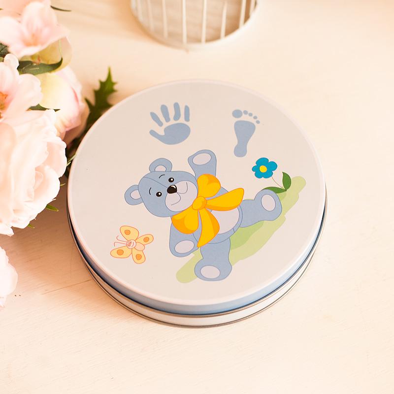 Okrągłe pudełko z masą na odcisk rączki i stópki dziecka. Idealny prezent na narodziny dla chłopca. Masa oraz pudełeczko jest w niebieskiej kolorystyce.