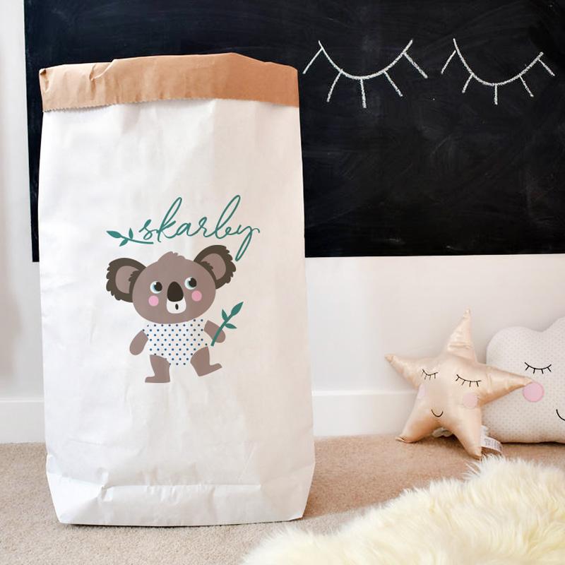 Biały wielki papierowy wór na zabawki dziecka, który jest ozdobiony grafiką z małymi misiem koala i napisem z imieniem dziecka