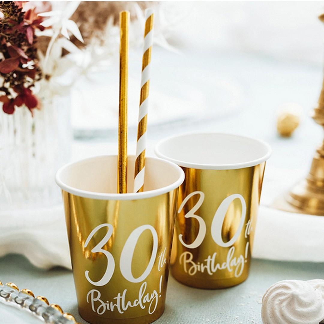 Kubeczki złote papierowe, które mają ozdobny biały napis 30th Birthday