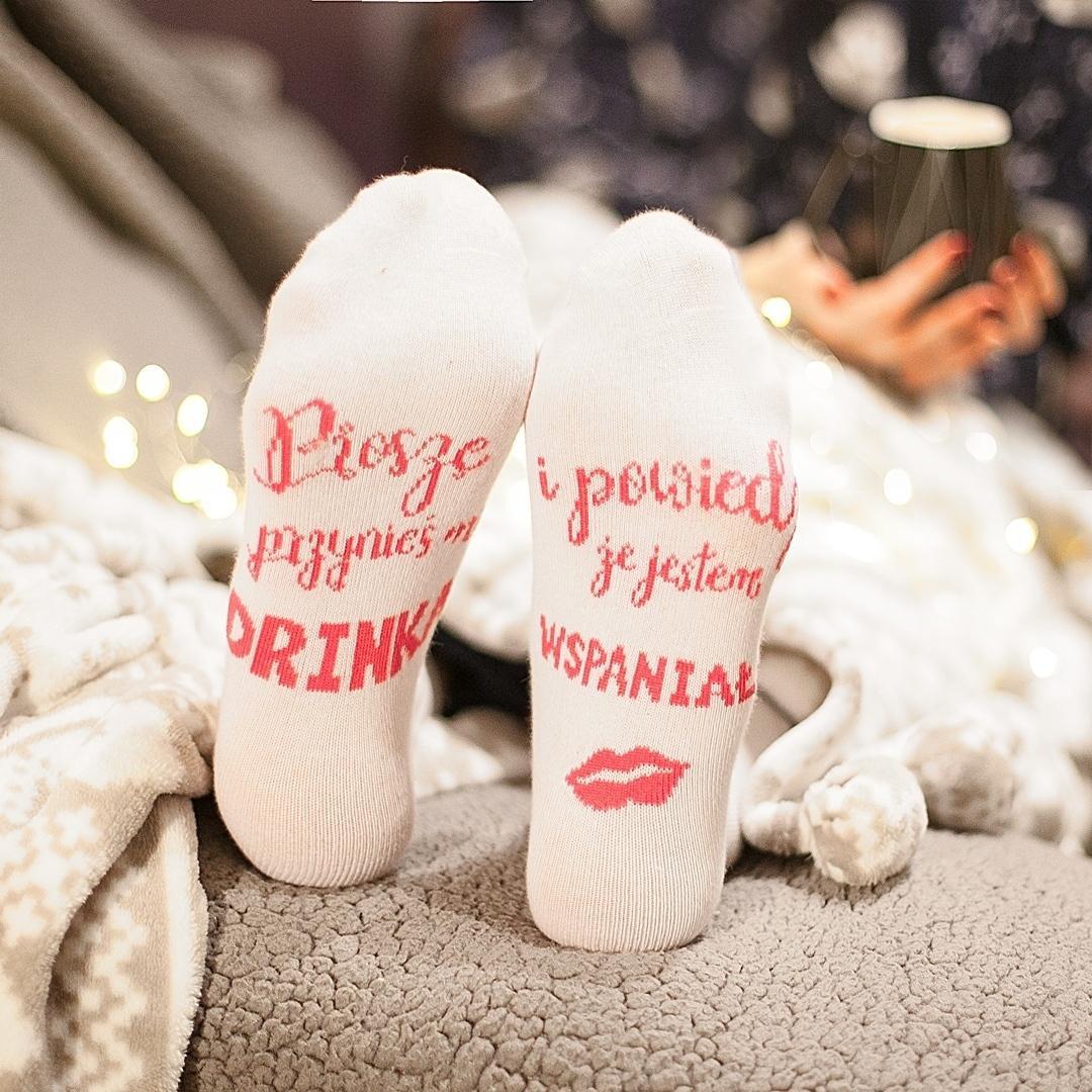 """Na zdjęciu na pierwszym planie są stopy w skarpetkach z napisem """"Prosze przynieś mi drinka i powiedz, że jestem wspaniała""""."""