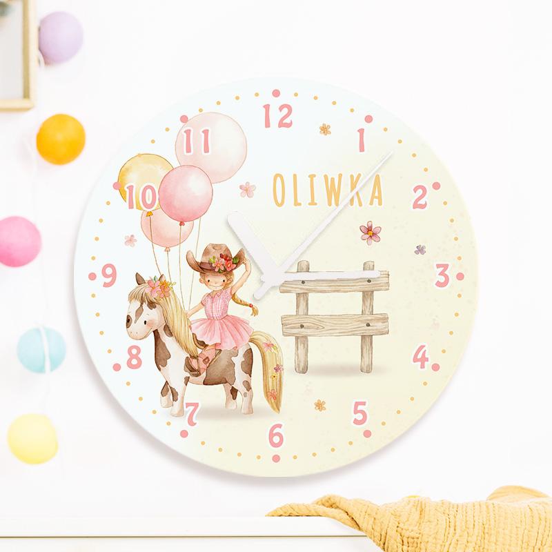 Personalizowany zegar z nadrukiem na którym widać małą kowbojkę na kucyku a obok niej jest imię dziecka