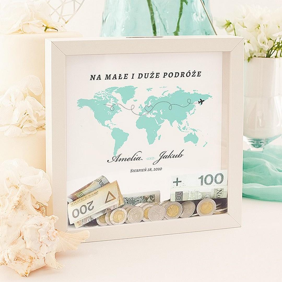 Skarbonka 3D w białej ramie z szybką z motywem kontynentów. Prezent ślubny, na którym są imiona pary i data ślubu