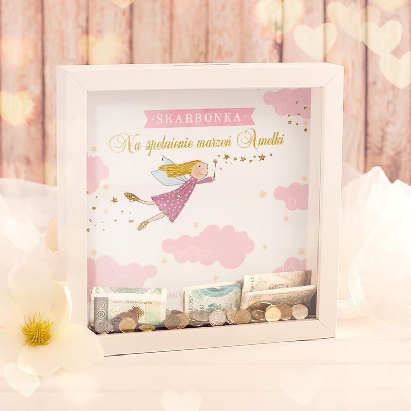 Skarbonka w przestrzennej ramce z dekoracją w postaci ozdobnej karty z nadrukiem w postaci dobrej wróżki i różowych chmurek. W skarbonce jest personalizowany podpis