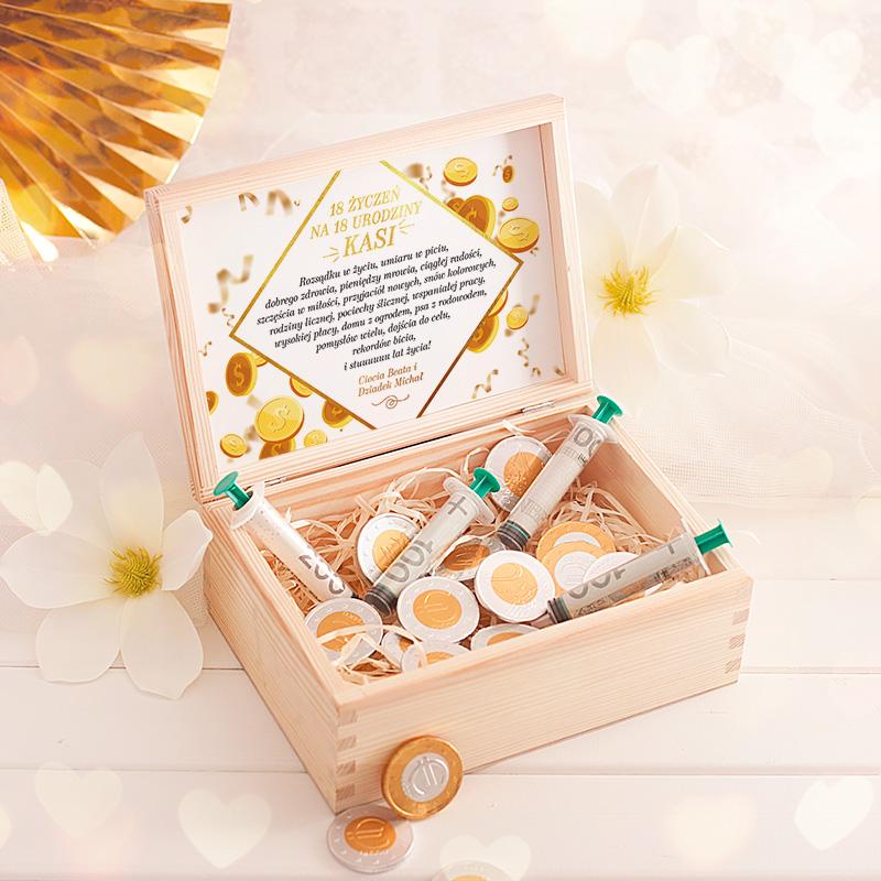 Skrzynka ze strzykawkami do wypełnienia banknotami oraz słodkie czekoladki w kształcie monet jako zastrzyk gotówki - prezent na 18 urodziny