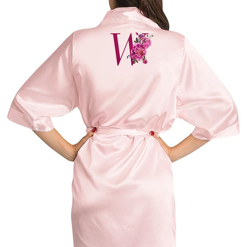 Różowy szlafrok z dużym inicjałem na plecach