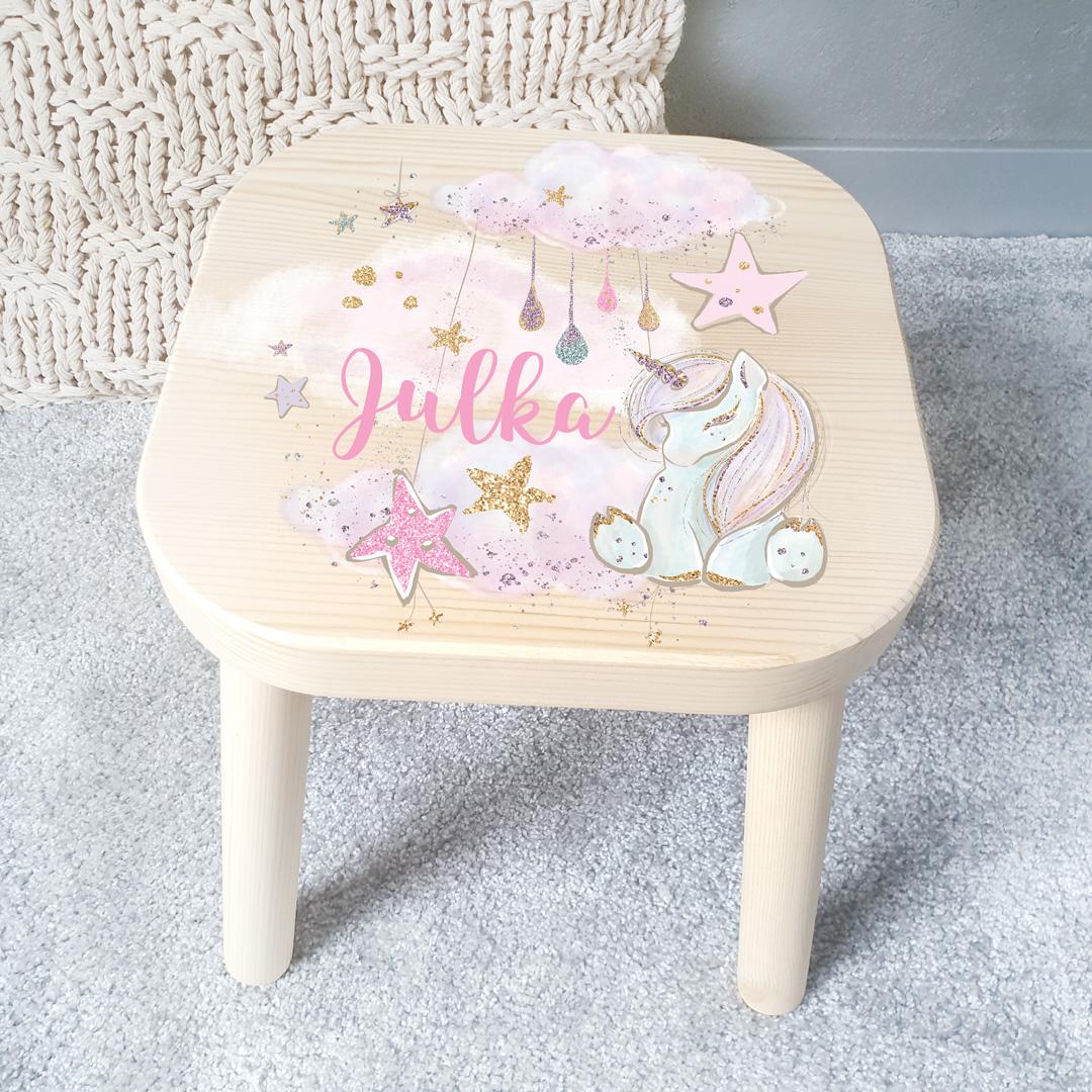 Drewniany taboret dla dziecka z nadrukiem na siedzisku, który przedstawia pastelowego jednorożca oraz imię dziecka w różowym kolorze, wokół znajdują się liczne ozdobniki - gwiazdki, kropki, chmurki