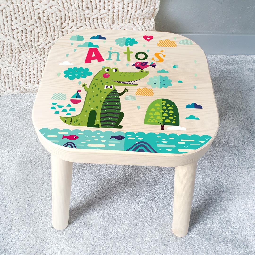 Stołek z kolorowym nadrukiem do pokoju dziecka, na którym widnieje wesoły krokodyl wśród chmurek i wody oraz imieniem dziecka