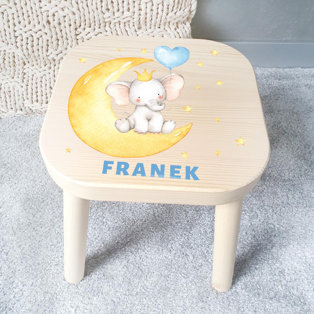 Stołek dziecięcy z jasnego drewna z nadrukiem na siedzisku w postaci słonika z balonikiem, który siedzi na księżycu. Wokół znajdują się liczne drobne gwiazdki, a pod grafiką jest imię dziecka