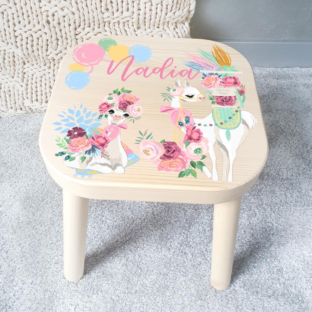 Drewniany stołek z kolorową dekoracją na siedzisku, która przedstawia dwie wystrojone lamy oraz wiele kolorowych akcentów, a nad rysunkiem widnieje różowy napis z imieniem dziecka