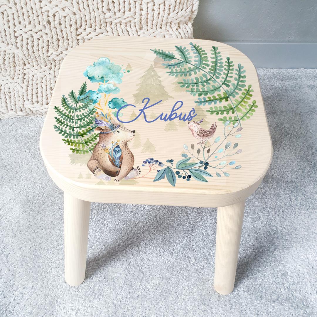 Stołek drewniany dziecięcy na którym znajduje się kolorowy nadruk w postaci leśnych zwierząt i roślin oraz imię dziecka