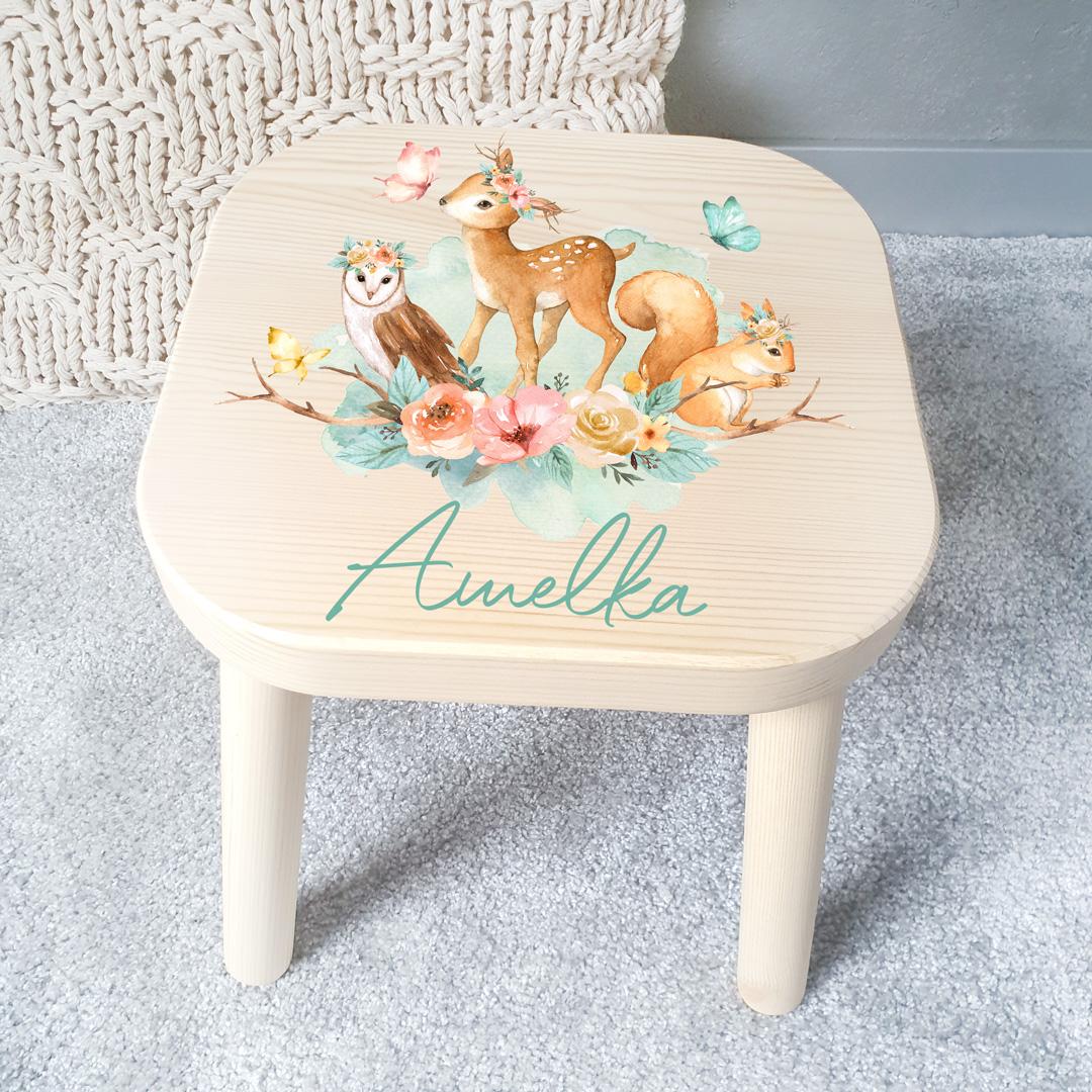 Stołek z jasnego drewna dla dziecka z kolorowym nadrukiem na siedzisku, na którym widać sarenkę, wiewiórkę oraz sowę. Pod rysunkiem znajduje się imię dziecka nadrukowane błękitną ozdobną czcionką