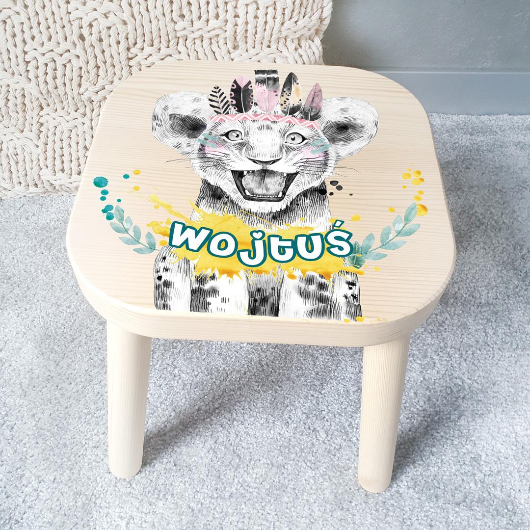 Taborecik z drewna dla dziecka z nadrukiem, który przedstawia małego, uśmiechniętego lwa z pióropuszem. Dodatkowo na krześle jest miejsce na imię małego właściciela siedziska
