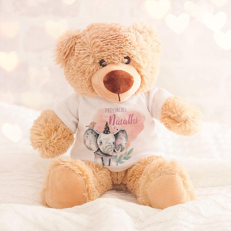 Pluszowy miś w kolorze jasnego beżu ubrany w białą koszulkę z grafiką uroczego słonika na tle różowego serca z imieniem dziecka