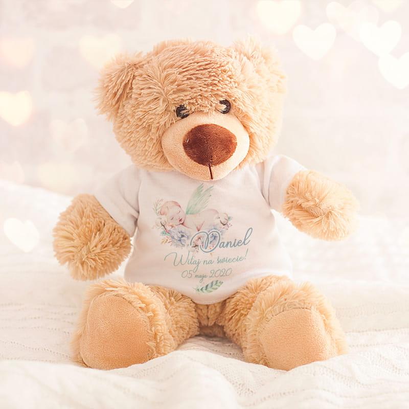 pluszowy miś w kolorze jasnego brązu w białej koszulce z krótkim rękawem, z wyjątkową grafiką na brzuszku w formie śpiącego chłopca na niebieskich kwiatkach, z imieniem i datą urodzenia dziecka