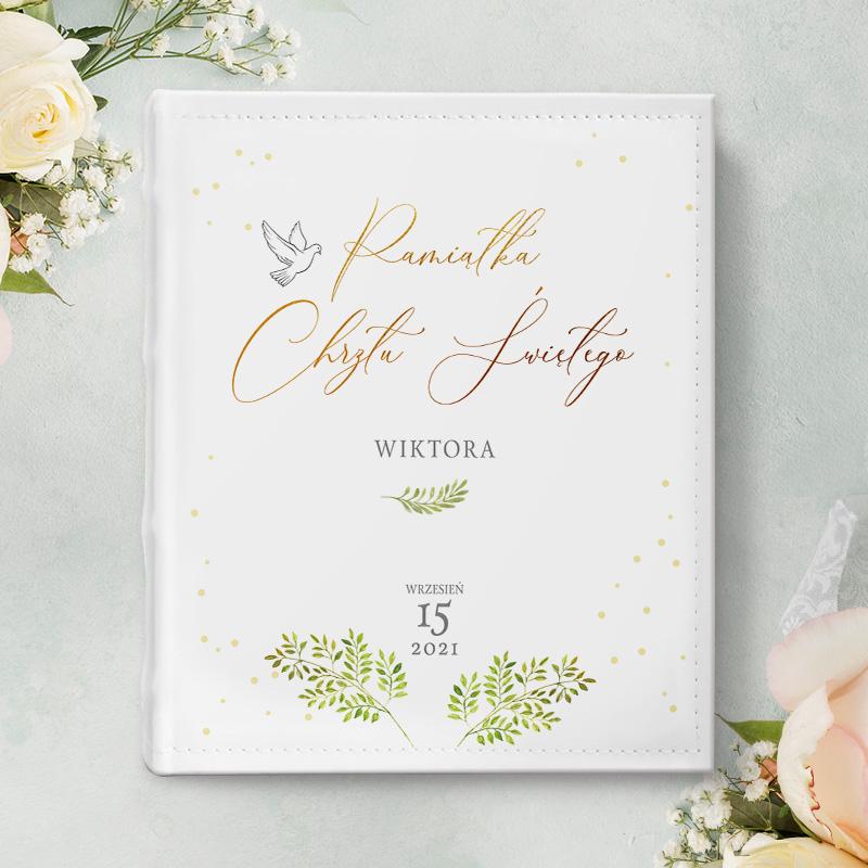 Album na zdjęcia z napisem pamiątka chrztu, imieniem dziecka oraz datą. Dodatkowo na albumie znajduje się motyw zielonych gałązek oraz symbol gołąbka.