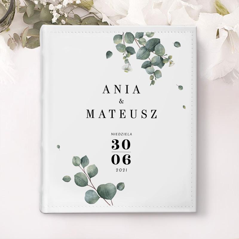 Album na zdjęcia w białej okładce z motywem gałązek eukaliptusa, imionami pary młodej, datą ślubu.