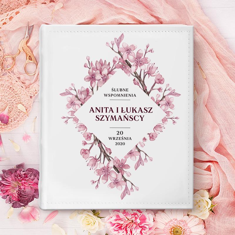 Album na zdjęcia z białą okładką na której są ozdobne kwiaty wiśni. W środku jest napis Wspomnienia ślubne z imionami i nazwiskiem młodej pary oraz datą ślubu. Album widać od frontu na dekoracyjnym, pastelowym tle.