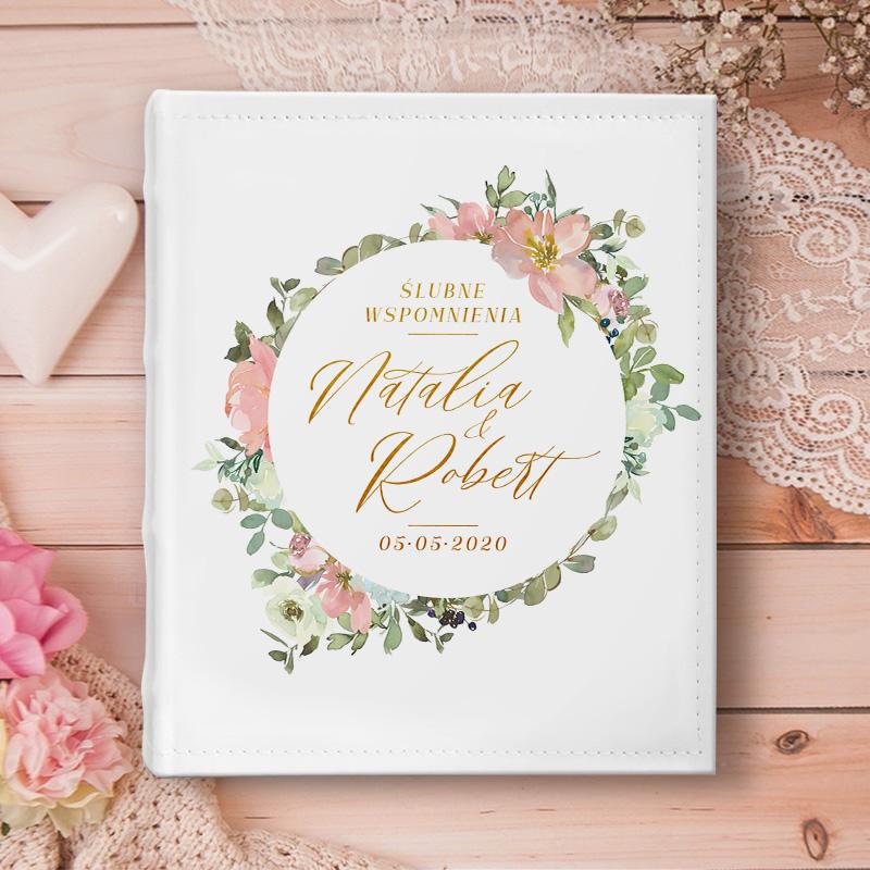 Biały album na zdjęcia z napisem na okładce: Wspomnienia ślubne z imionami pary młodej i datą ślubu w środku koła. Wokół napisu jest duży kolorowy wianek z kwiatów. Alubm leży na drwnianym stole