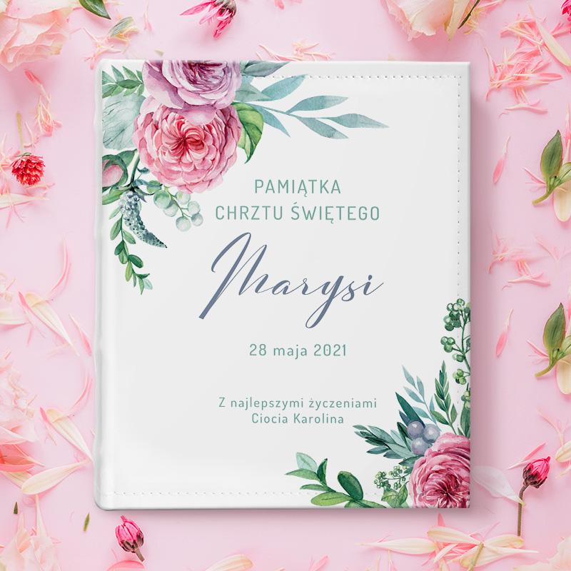 Album na zdjęcia z dekoracją na rogach w postaci kwiatów. Na środku jest napis Pamiątka Chrztu Świętego który jest do uzupełnienia personalizacją. Album jest na różowym tle.