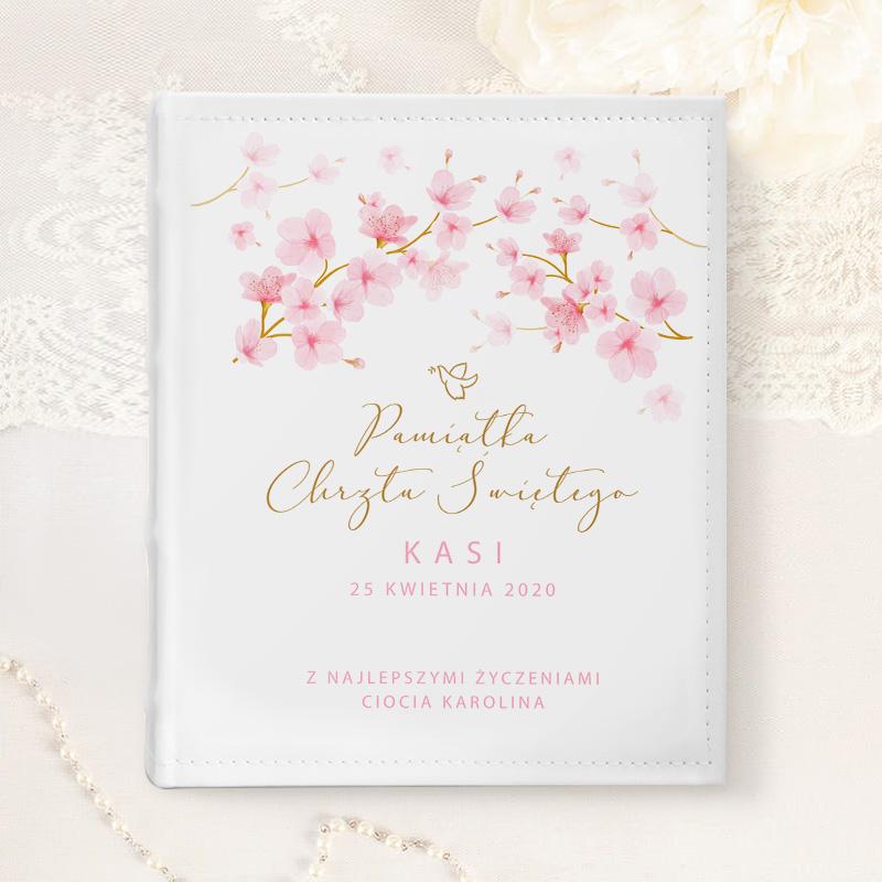 Biały album na zdjęcia z personalizowaną okładką, Z przodu jest dekoracaja z kwiatów magnolii oraz personaliozowany podpis z imieniem dziecka, datą chrztu oraz dedykacją. Album jest na białym tle