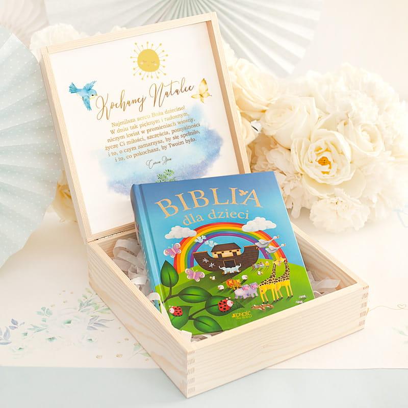 Personalizowana skrzynka wykonana z jasnego drewna, wieczko z grafiką sarenki i zajączka przy łódce, z ilustrowaną biblią dla dzieci