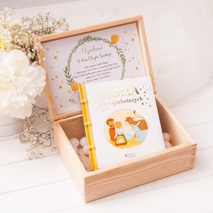 Drewniane pudełko w jasnym kolorze z biblią dla dzieci. Wewnątrz znajduje się personalizowana karta z dedykacją. Wieczko skrzynki posiada do wyboru zdobienie ażurowe lub grawerowane.