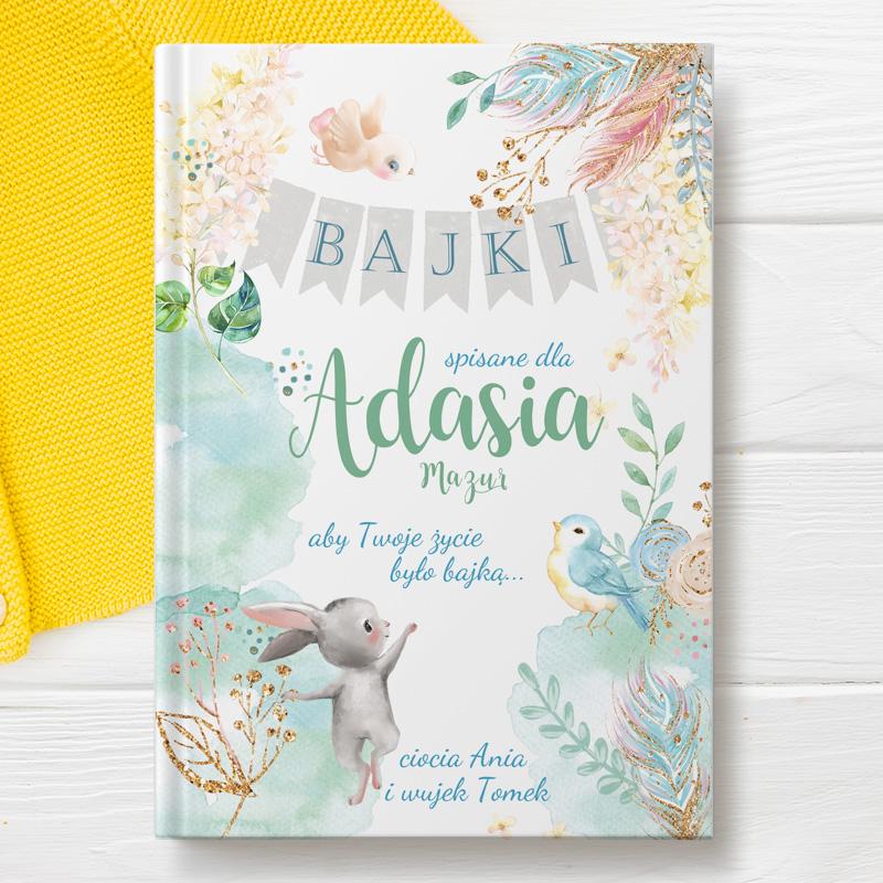 Książka dla dzieci z opowiadaniami i personalizowaną okładką na której widnieje napis Bajki z imieniem dziecka i dedykacją. Okładkę zdobi uroczy rysunek króliczka oraz pastelowymi dekoracjami.