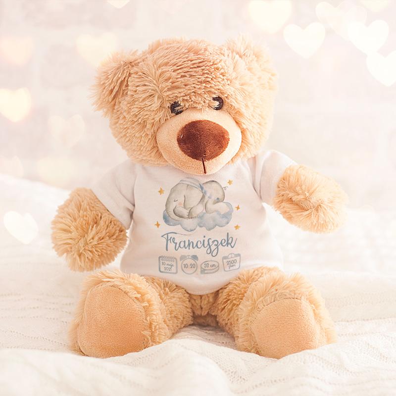 Miękki, pluszowy miś w kolorze beżu, w białej koszulce z krótkim rękawem z grafiką uroczym śpiącym słonikiem w chmurach i imieniem dziecka i metryczką