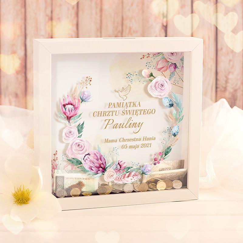 Skarbonka w ramce z szybką z pleksi na któej jest trójwymiary napis z dekoracyjnymi kwiatkami. Prezent na chrzest dziecka z imieniem