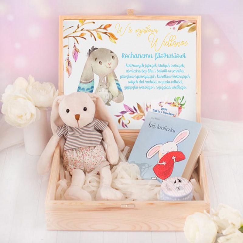 Drewniana otwarta skrzynka, w której jest maskotka zajączka i książeczka dla dzieci oraz okrągłe pudełeczko. Na wieczku jest karta z życzniami dla dziecka i bilecikiem na klamerce z podpisem od kogo jest prezent