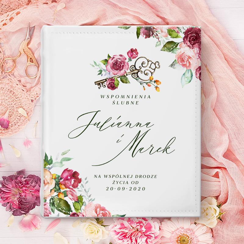 Okładka albumu na zdjęcia z kwiatami, imionami młodej pary, napisem wspomnienia ślubne i datą. Na górze jest także klucz. Album leży płasko na różowym bieżniku