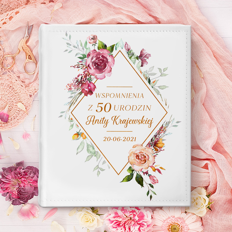 Okładka albumu z rombem, który ma kwiaty wokół a w środku jesy napis Wspomnienia z urodzin z imieniem i nazwiskiem oraz datą. Album ma białą okładkę i leży na płasko na różowym bieżniku