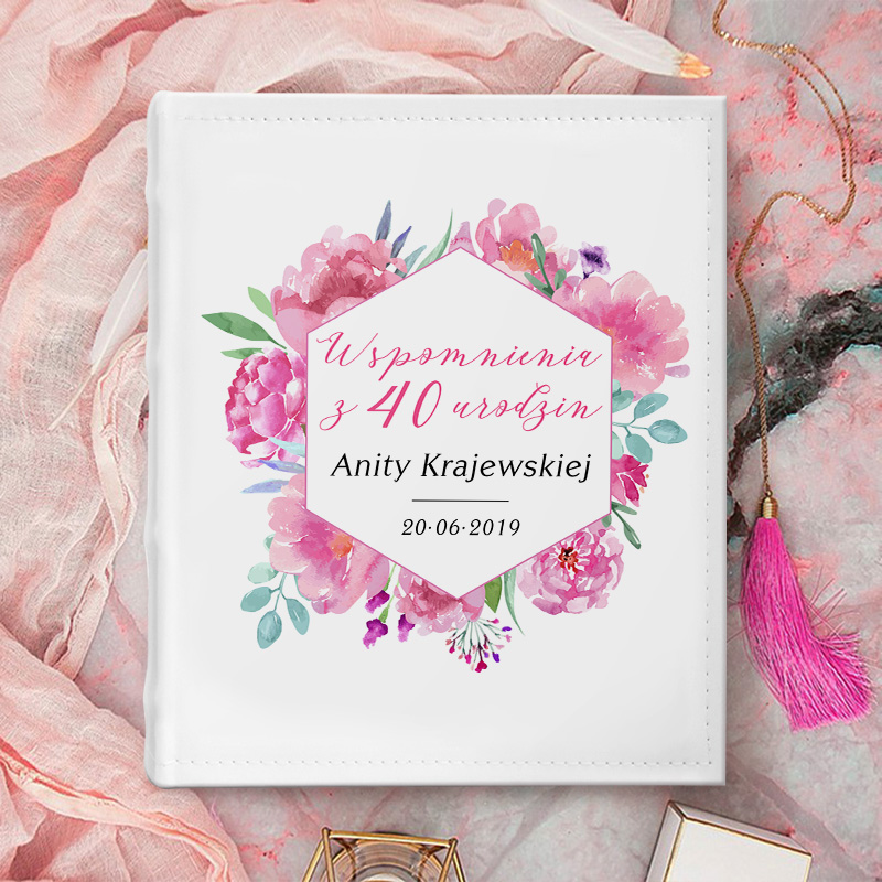 Album na zdjęcia z ramką i różowymi kwiatami na okładce. W ramce jest różowy napis Wspomnienia z urodzin i imię oraz data. Album ma biały kolor.