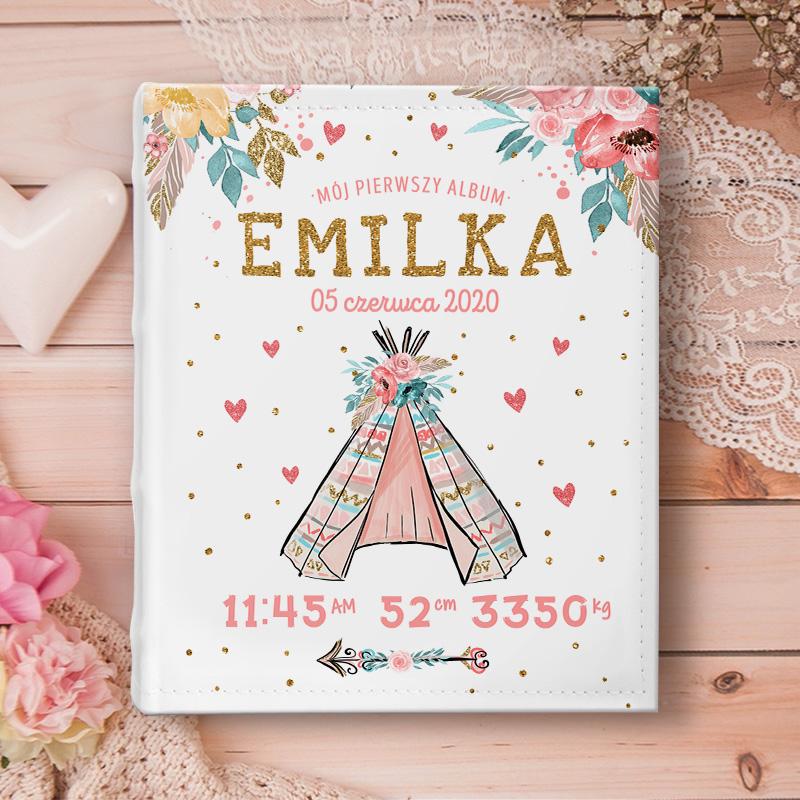 Album na zdjęcia z okładką z metryczką i namiotem indiańskim. Nad namiotem jest imię dziecka, różowe kwiaty i tytuł albumu. Album dla dziewczynki leży na drewnianym stole.