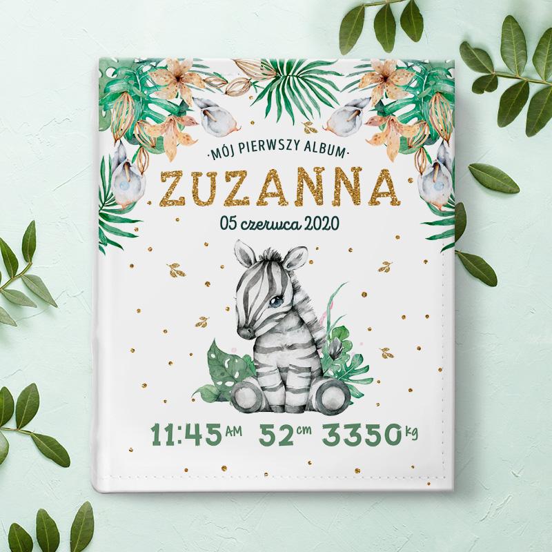 Okładka jasnego albumu na zdjęcia z motywem małej zebry która siedzi. Wokól postaci są informacje z metryczki dziecka o imieniu Zuzanna. Na górze okładki są zielone, tropilkalne liście.