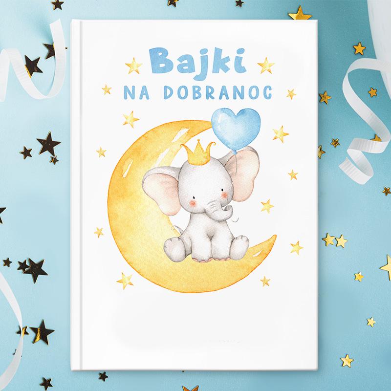 Książka z bajkami dla dzieci ze słonikiem na księżycu na okładce. Napisy mają niebieski kolor i zawierają imię dziecka i miejsce na dedykację