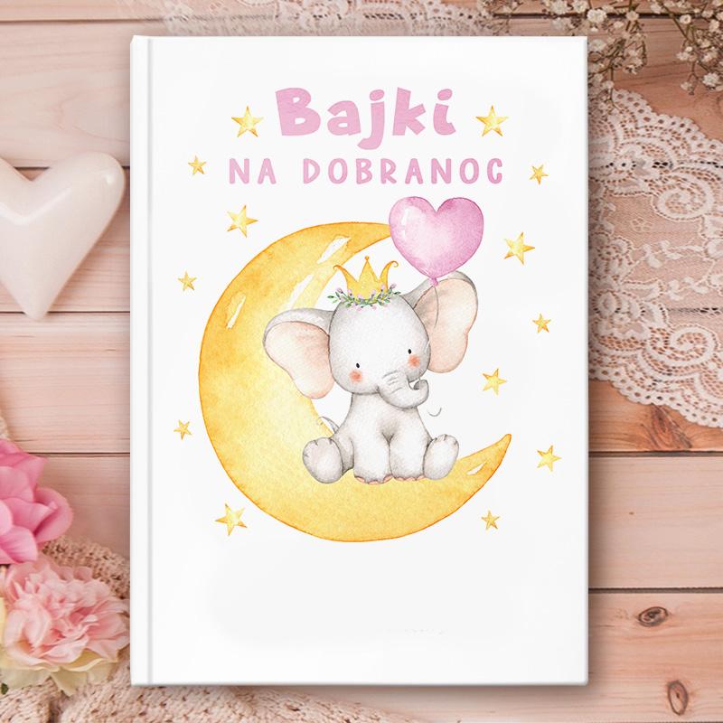 Książka z bajkami dla dzieci ze słonikiem na księżycu na okładce. Na dole okładki jest miejsce na imię dziecka i podpis. Napisy są różowe
