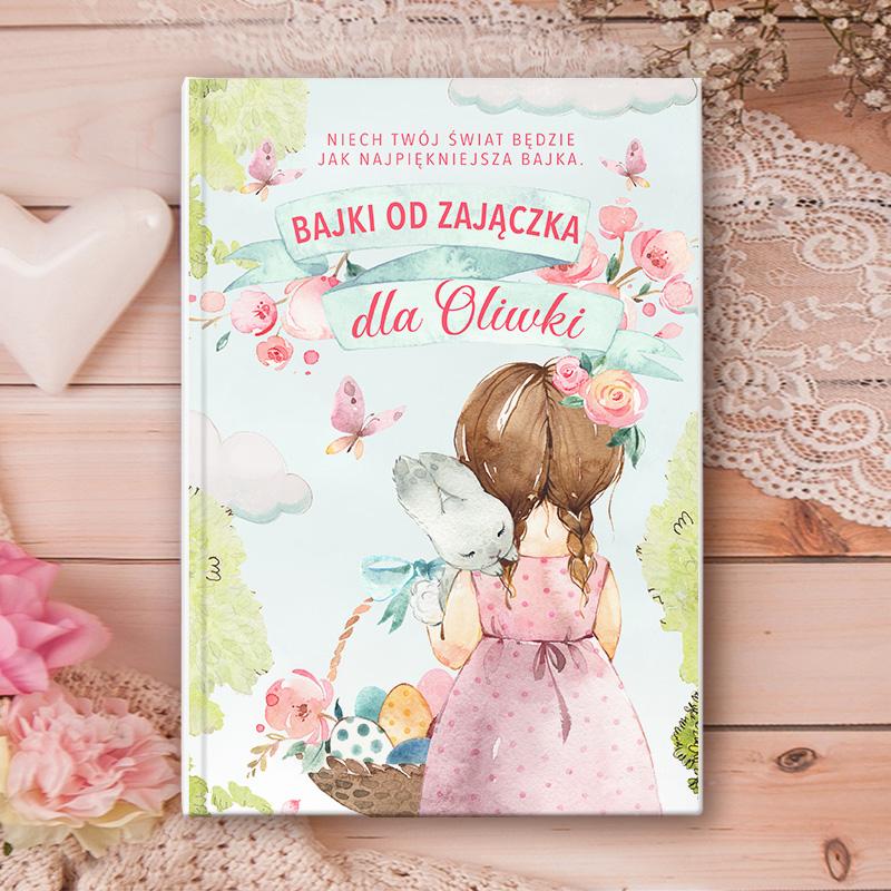Okładka książki z dziewczynką która ma na ramieniu zajączka i trzyma koszyk wielkanocny. Nad rysunkiem jest napis Od Zajączka Dla ... oraz dedykacja.