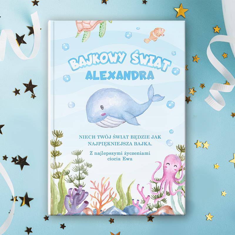 Książka dla dzieci z morską okładką, na której jest niebieski wieloryb i inne zwierzęta morskie. Na okładce jest napis Bajkowy świat i podpis z dedykacją. Okładka ma niebieskie tło.