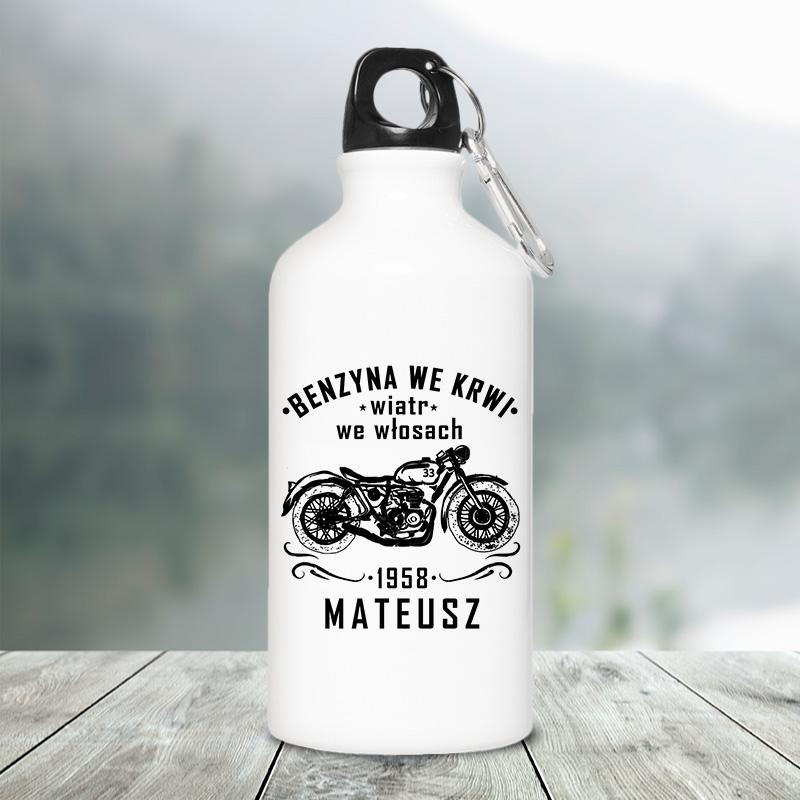 Bidon na wodę z czarnym korkiem, który ma karabińczyk. Bidon jest biały i ma czarny nadruk motocyklisty na motorze oraz napis z imieniem.