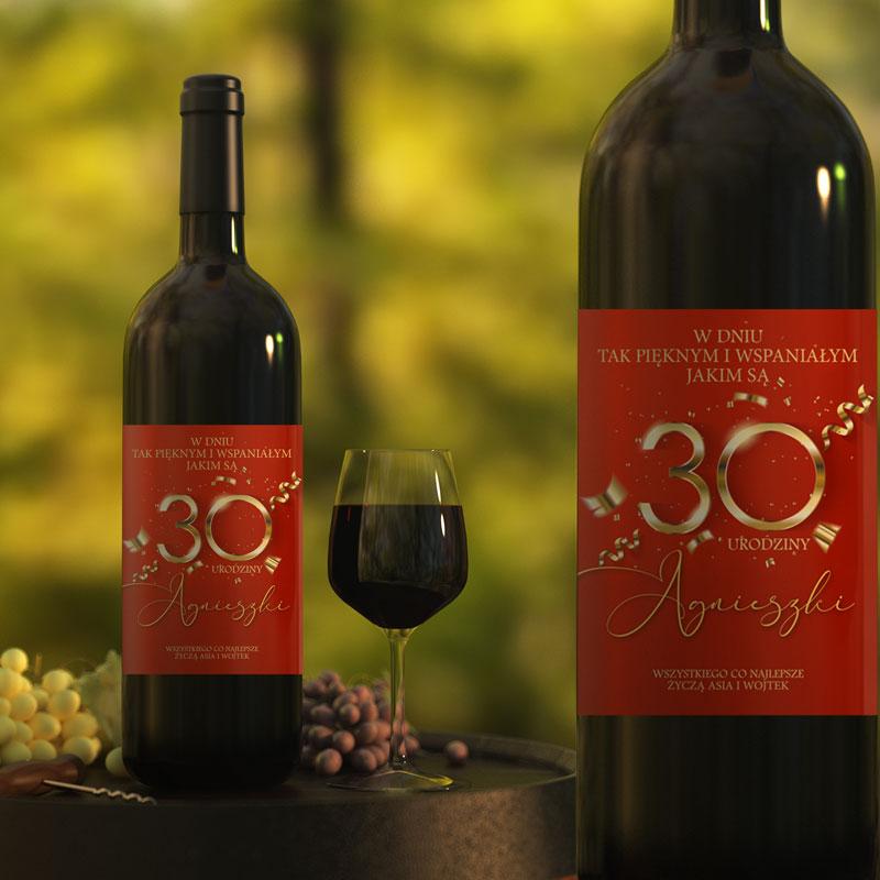Butelki z winem na których jest etykieta z czerwonym tłem i złotym napisem 30 urodzini z imieniem i podpisem od kogo. Butelka z winem stoi na stole, obok jest kieliszek pełny do połowy.