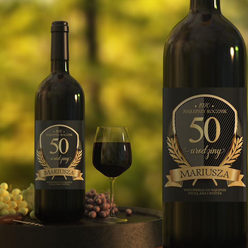 Butrlka z etykietą na 50 urodziny. Na czarnym tle nakjelki są złote napisy z 50 oraz imieniem i podpisem od kogo. Widok z bliska ora z daleka butelki na wino.