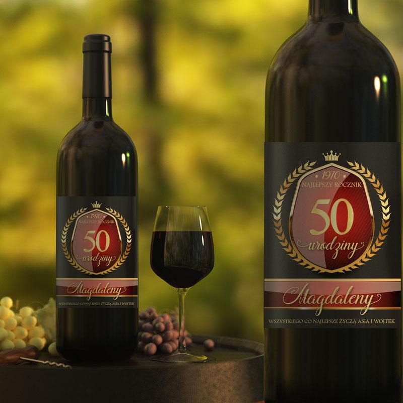 Butelka z winem, na której jest etykieta z napisem na 50 urodziny. Tło etykiety jest czarne a napisy złote na czerwonym tle. Widok etykiety z bliska i z daleka na butelce z winem