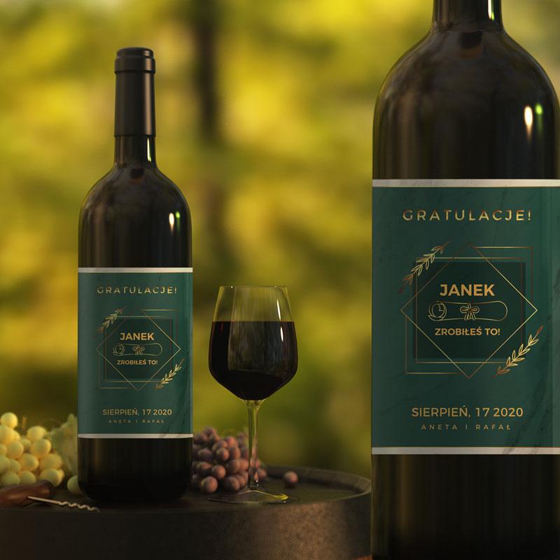 Butelka z winem na której jest etykieta z zielonym tłem i złotymi napisami. Etykieta ma napis gratulacje oraz podpis od kogo i datę. Zdjęcie pokazuje butelkę z etykietą z daleka i zbliżenie.
